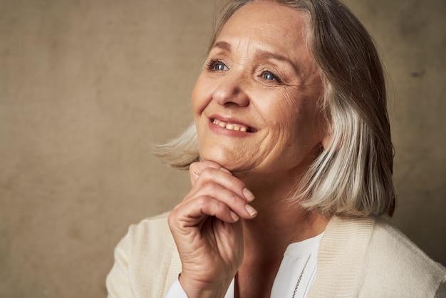 Пожилая женщина в халате лицо крупным планом позирует на изолированном фоне