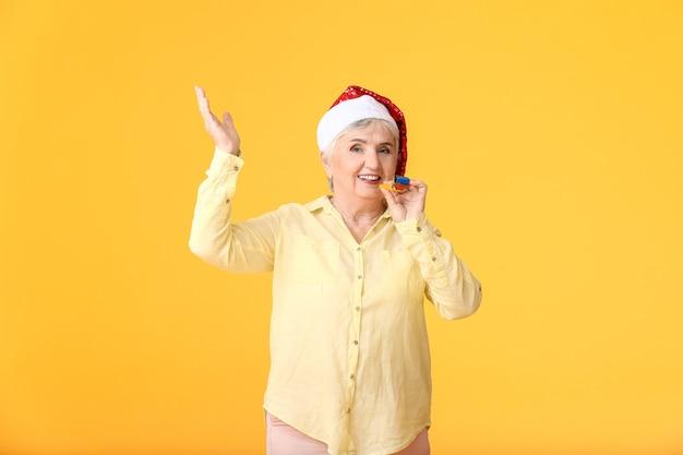 色のサンタ帽子の年配の女性