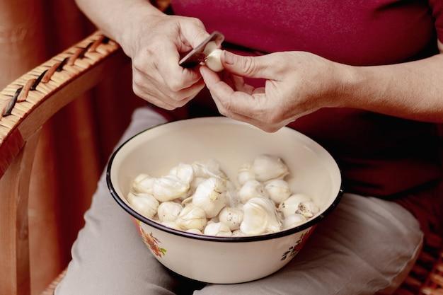 台所の年配の女性が包丁でにんにくを切る。キッチンで働き、料理をする