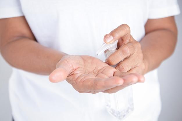 흰 옷을 입은 노인 여성이 알코올 젤로 손을 씻습니다.