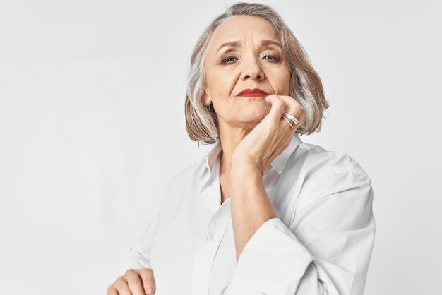 Пожилая женщина в белой рубашке эмоции светлом фоне