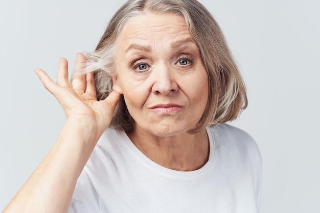 흰색 티셔츠를 입은 노인 여성 통증 건강 문제 불만 치료. 고품질 사진