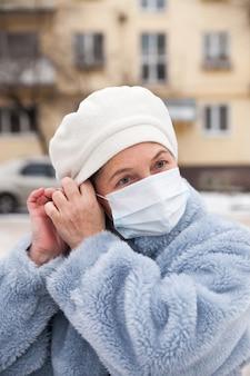 Пожилая женщина в зимней одежде и медицинской маске на улице. тема защиты во время вспышки коронавируса