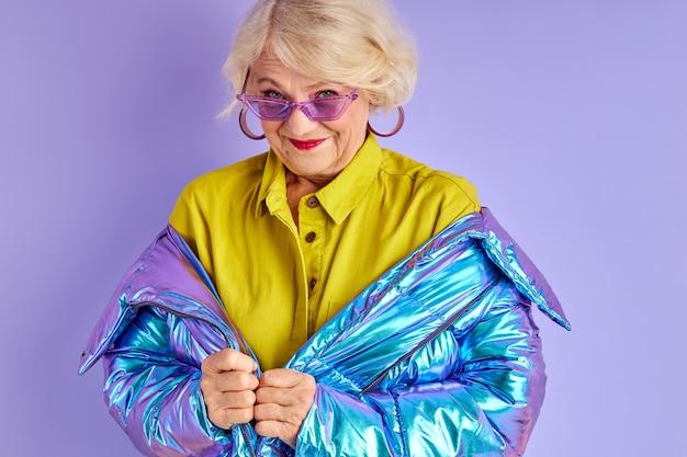 冬の服とサングラスでカメラに向かってポーズをとる年配の女性、ファッショナブルな派手な服装で、紫色の空間に隔離され、散歩の準備をして、お楽しみください