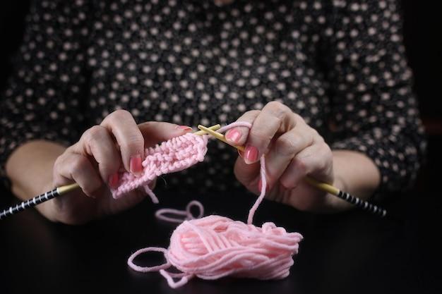 Пожилая женщина занимается вязанием теплых свитеров для внуков