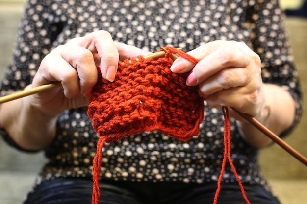Пожилая женщина занимается вязанием теплых свитеров для внуков.