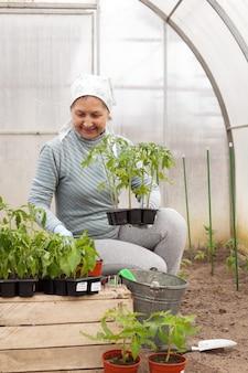 Пожилая женщина занимается посадочными работами в теплице