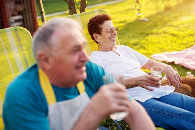 Пожилая женщина сидит снаружи на ленивом стуле, смеется и пьет воду, в то время как ее муж сидит рядом с ней.