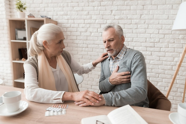 Elderly woman is worried because of pain in husband's heart.