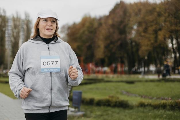 コピースペースで屋外でジョギングする年配の女性