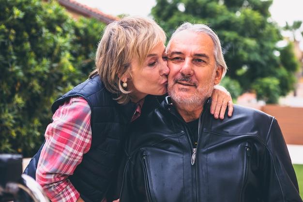 Elderly woman kissing man on cheek