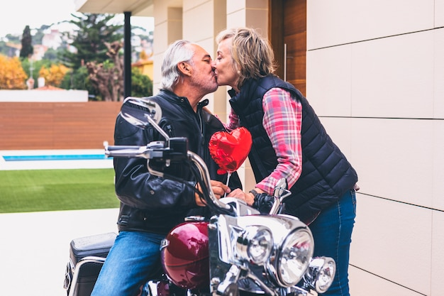 Elderly woman kissing man on motorcycle