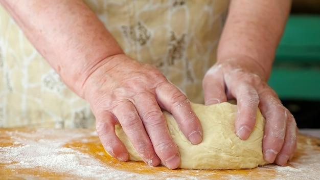 年配の女性が生地をこねます。手のクローズアップ。