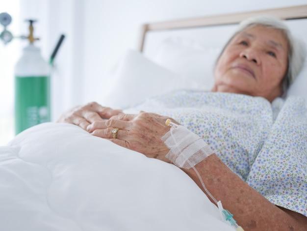 病院のベッドに横たわっている高齢の女性。