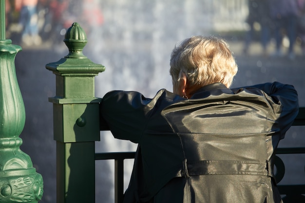 Elderly woman leaned on the railing of the bridge and looks at the fountain