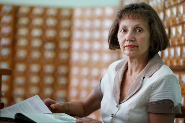 Пожилая женщина-библиотекарь с книгой на фоне библиотечных шкафов с ячейками.