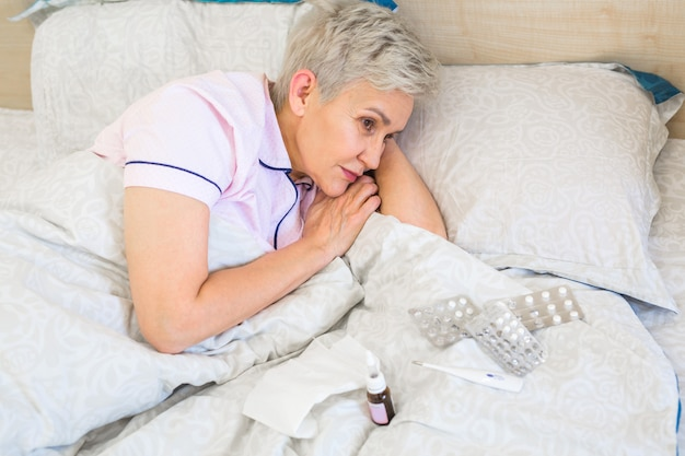 Пожилая женщина лежит на кровати с таблетками
