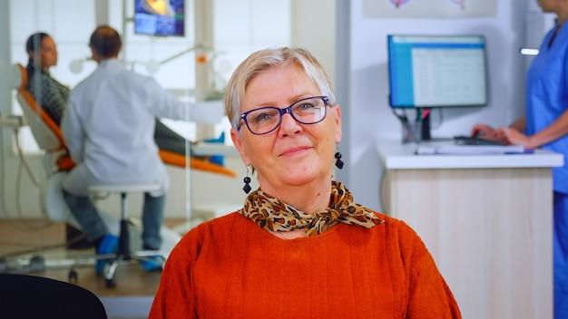 Пожилая женщина, глядя на камеру, пока врач осматривает пациента в фоновом режиме. старшая дама улыбается на веб-камеру, сидя на стуле в зале ожидания стоматологической клиники, помощник печатает на компьютере
