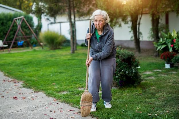 家の裏庭でほうきを押しながらカメラを見て高齢者の女性。