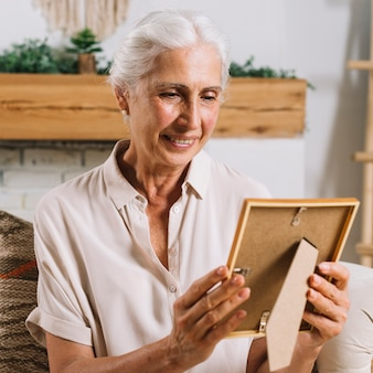 An elderly woman looking at photo frame