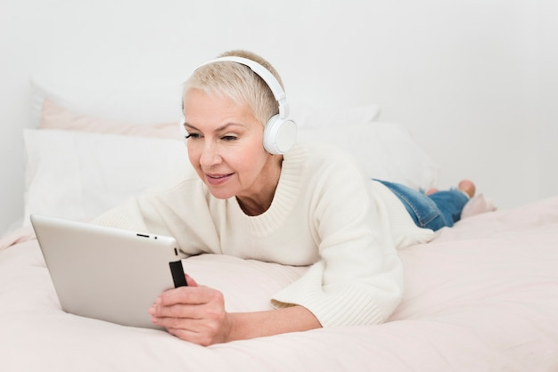 Elderly woman looking at tablet and listening to music on headphones