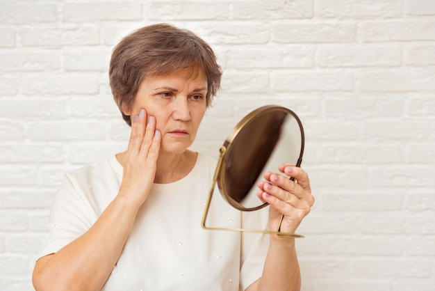 Elderly woman looking at wrinkled face in mirror