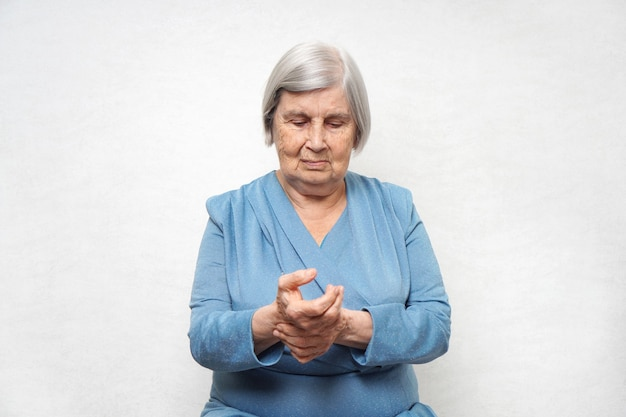An elderly woman measures the pulse on her hand