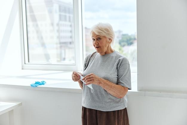 年配の女性の医療マスクのパンデミック保護。高品質の写真
