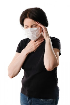 An elderly woman in a medical protective mask, with a sore throat and a headache, on a white surface.