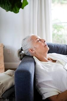 Пожилая женщина дремлет на диване