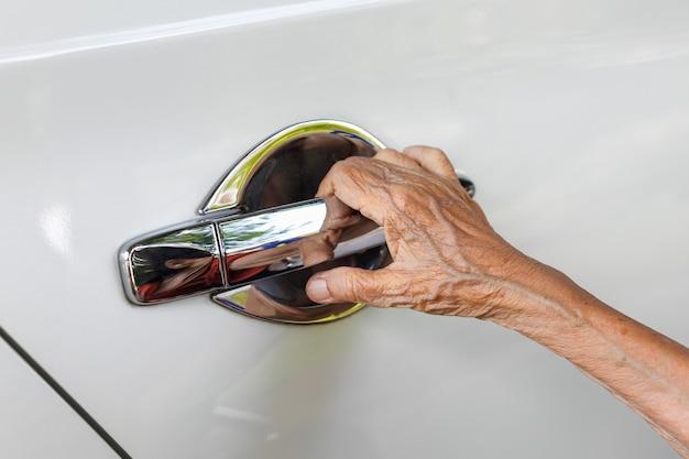 Elderly woman open the car door