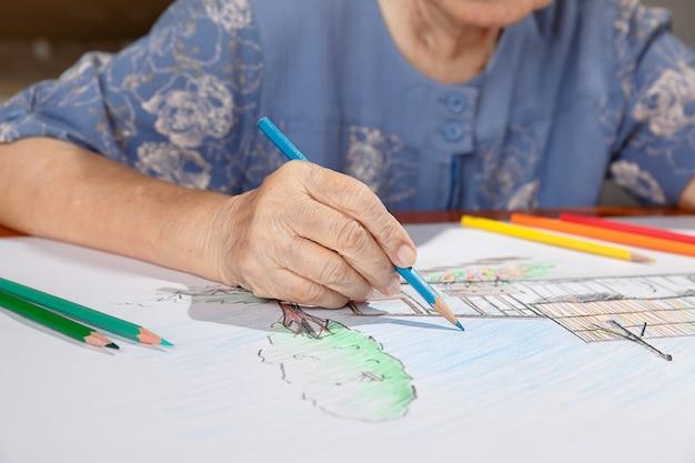 娘と一緒に絵に色を塗る年配の女性、自宅での趣味