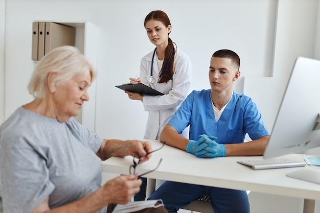 의사 간호사와 의료 사무실에서 리셉션에서 노인 여성 환자
