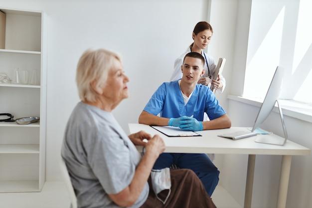 Пожилая женщина-пациент на приеме у врачей и медсестры