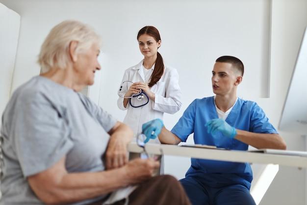 Пожилая женщина-пациент в кабинете врачей с медсестрой общается