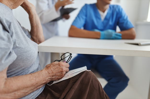Пожилая женщина-пациент с очками в руках в больнице на приеме у врачей