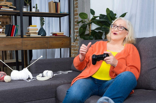Elderly woman playing play station with joy pads