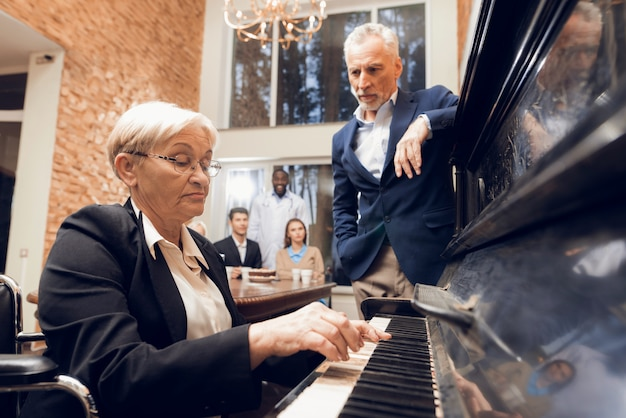 An elderly woman plays the piano at a nursing home