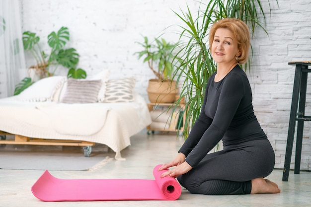 An elderly woman poses after her workout with a fitness mat. women fitness and age concept.