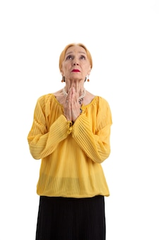 Elderly woman praying isolated old lady looking up hope for a miracle