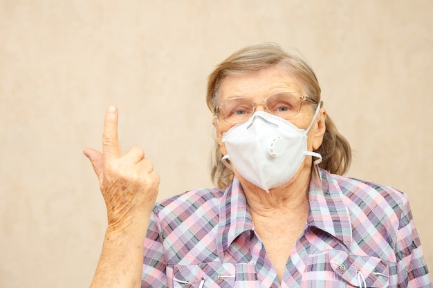 Elderly woman in protective mask points up