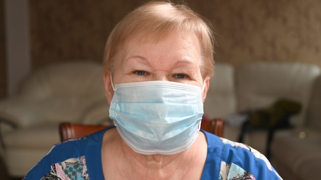 Elderly woman puts on a face protective mask. life during a pandemic and quarantine.