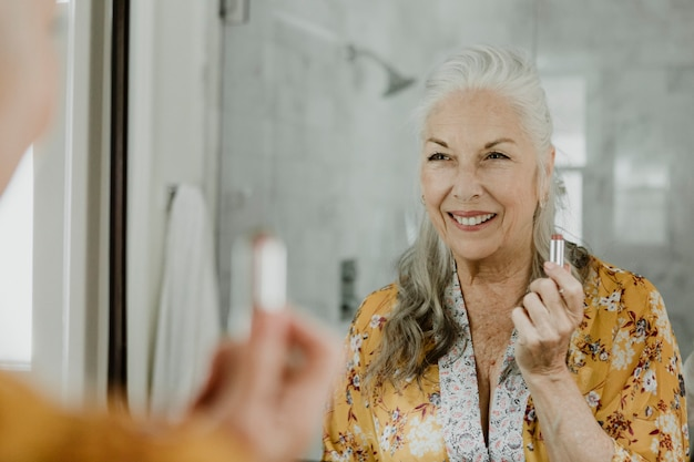 Elderly woman putting on a makeup in front of a mirror