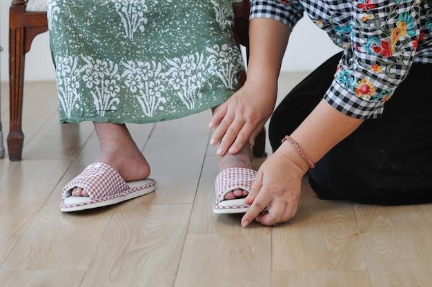 Пожилая женщина надевает тапочки дочерью
