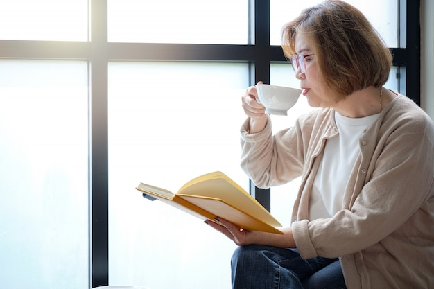 Elderly woman reading a book by the window on relaxing day with a cup of coffee.