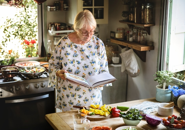 Elderly woman reading a cookbook in the kitchen