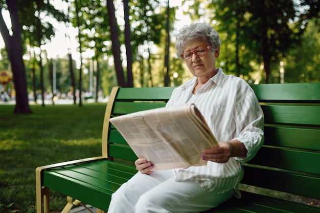 An elderly woman reading newspaper on the bench in summer park. aged people lifestyle. pretty grandmother having fun outdoors, old female person on nature