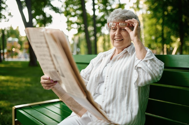 An elderly woman reading newspaper on the bench in summer park. aged people lifestyle. pretty grandmother having fun outdoors, old female person outdoors
