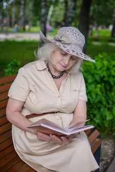 An elderly woman reads a book in the park