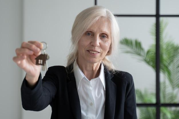Пожилая женщина агент по недвижимости с ключами от квартиры в руках